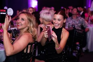 Guests in cocktail dress smiling and taking photos at their tables at the Most Wanted Awards Grand Final 2019